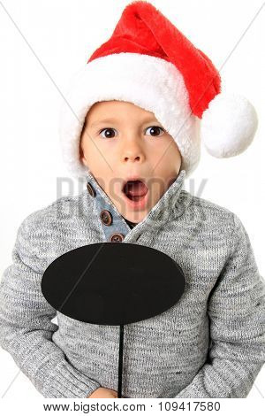 Five year old boy wearing a Santa hat holding a speech bubble. Add your own text.