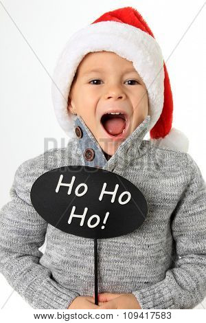 Five year old boy wearing a Santa hat holding a speech bubble.