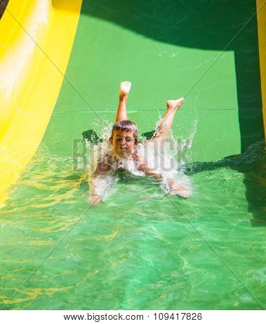 Child Playing On Water Slide