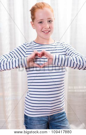 Portrait Teenage Girl Forming Heart Shape With Hands