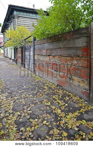 Sidewalk with fallen yellow leaves and old wooden shabby fence. Irkutsk street, Russia