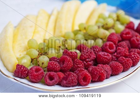 Pineapple, Grapes And Raspberries On A Plate