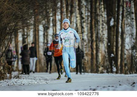 old man runner running on track in winter forest