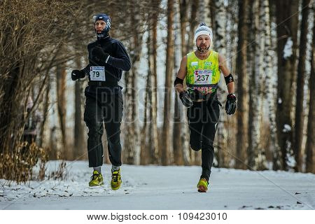 two athletes middle-aged men running down track in winter forest