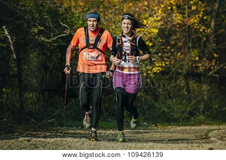 running along an old man and young woman in autumn forest