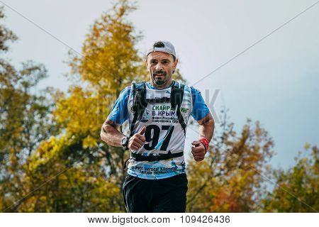 middle-aged man running around  forest with a backpack