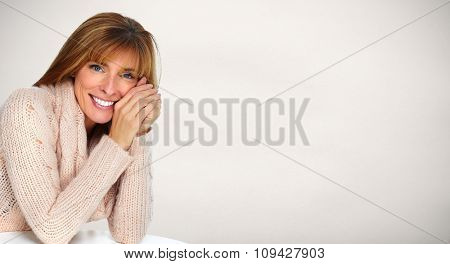Beautiful casual woman portrait over grey wall background.