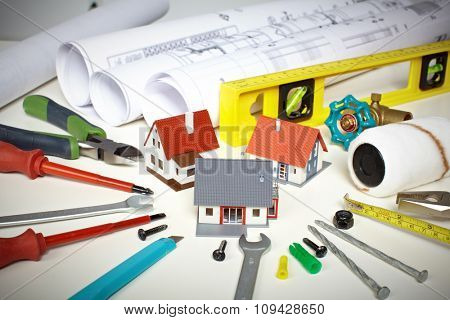 Little house and construction tools. Renovation background.