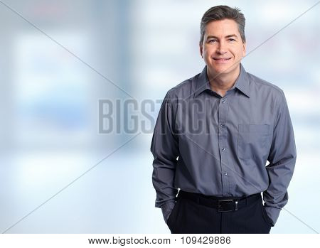 Handsome smiling businessman over blue background.