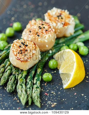 Scallops With Sesame Seeds, Asparagus, Lemon And Green Peas On A Black Plate