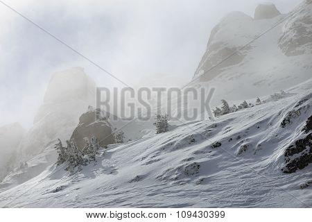Snowy mountain peaks in fog