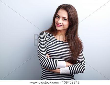 Cute Smiling Casual Woman With Folded Hands Looking Happy On Blue Background With Empty Copy Space
