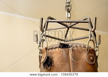 Brown Leather Punching Box On A Metal Chain Close Up With Plenty Copy Space