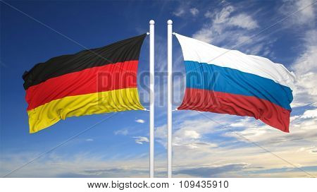German and Russian flags against of blue sky