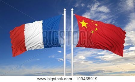French and Chinese flags waving against of blue sky