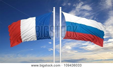French and Russian flags waving against of blue sky