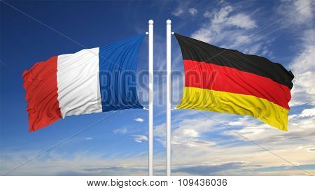 French and German flags waving against of sky
