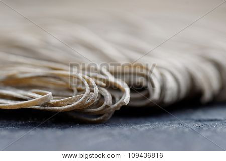 Squid ink pasta on wooden board, macro shot