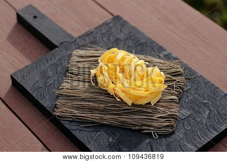Two types of pasta on old cutting board, sunlight, outdoor shot