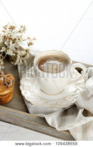 Cup of coffee and pile of tasty cookies with chocolate crumbs on wooden tray