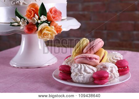 Beautiful wedding cake decorated with flowers and plate with cakes on pink table against brick wall background, close up