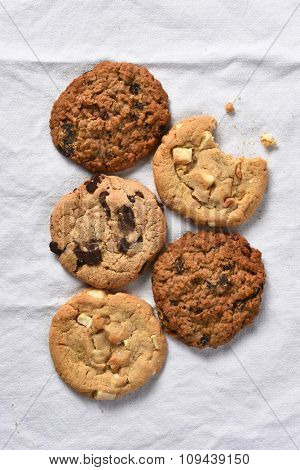 High angle view of five cookies one with a bite taken out of it. Vertical format on a white kitchen towel.
