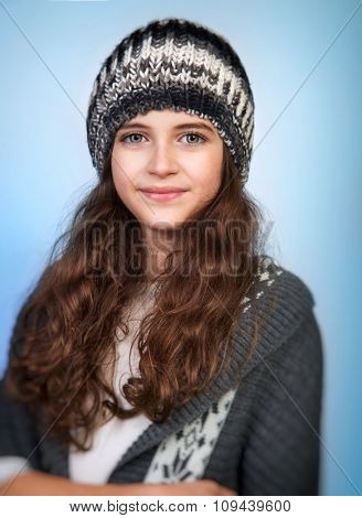 Portrait of cute teen girl wearing stylish knitted hat and sweater isolated on blue background, winter fashion for teenagers