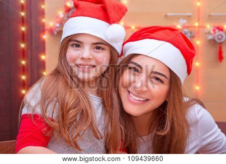 Closeup portrait of mother with cute little daughter wearing Santa hat baking cookies on the kitchen at home, enjoying traditional Christmas preparation