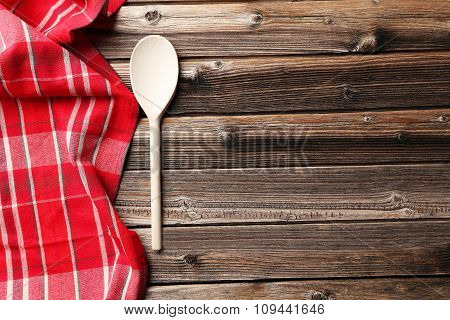 Empty Wooden Table With Wooden Spoon And Napkin On Brown Background