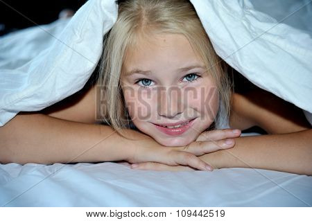 Beautiful cheerful girl looks out from under a blanket