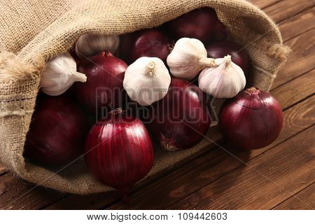 Scattered bag with red onions and garlic on wooden background