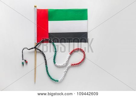 Mini flag of UAE and an Islamic rosary. National day celebration objects.