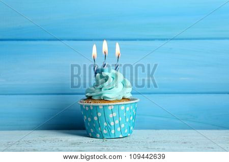 Sweet cupcake with candles on blue wooden background