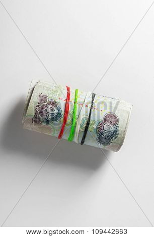 UAE dirham currency. Five hundred dirham notes rolled with rubber bands of national flag colors. A Concept.
