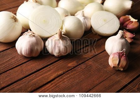Fresh whole peeled onions with garlic on wooden background