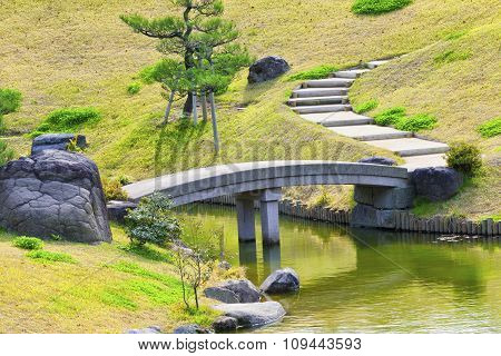 Grey stone bridge and uphill pathway