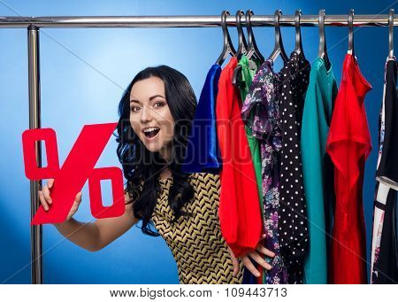 Happy Woman Holding Percent Sign At The Clothing Rack With Dresses