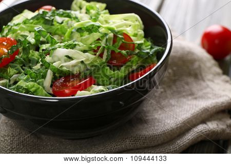 Savoy cabbage and tomato salad served in bowl on wooden table
