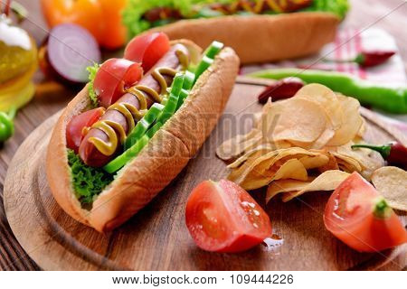 Hot dog and vegetables on wooden cutting board