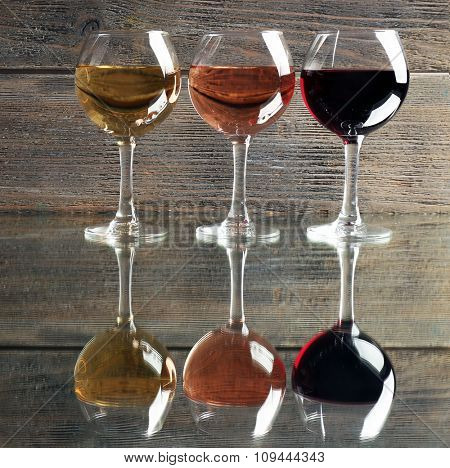 Glasses with white, rose and red wine on wooden background, close up