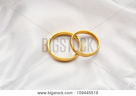 Golden Wedding Rings On A White Satin