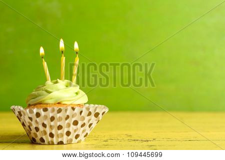 Tasty cupcake with candles on yellow wooden table against green background