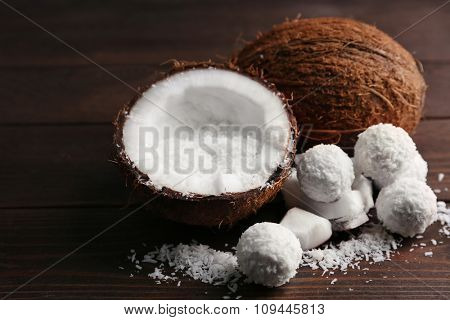 Candies in coconut flakes and fresh coconut on dark wooden background