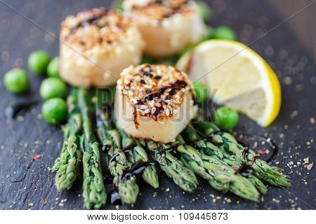 Fried Scallop  With Sesame Seeds And Balsamic Sauce, Asparagus, Lemon And Green Peas On A Black Plat
