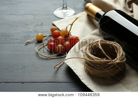Bottle of wine and grape on wooden table