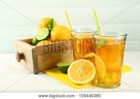 Iced tea with lemon on light wooden background