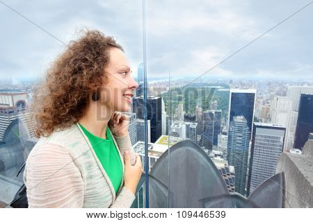 woman looks at Central Park through the glass on roof of a skyscraper