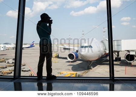 silhouette of a boy photographing a plane through the window of Airport