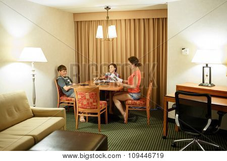 Mom with two kids read magazines at the table