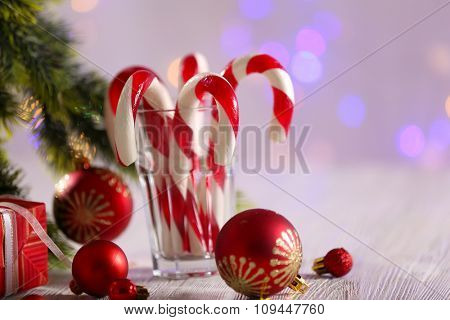 Christmas Candy Canes in glass on table on light background